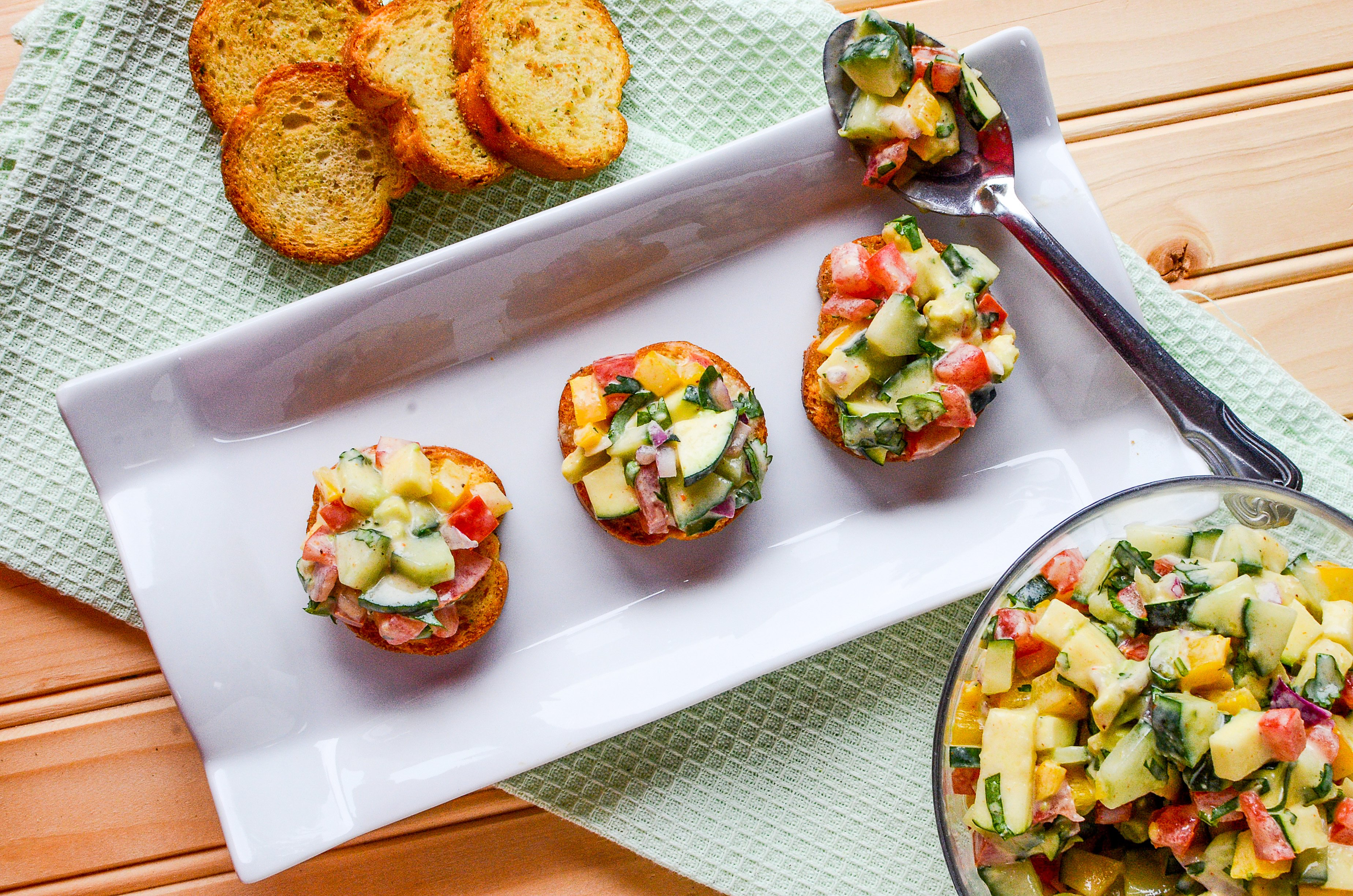 A top down photo of a Cucumber avocado salsa on small baguettes and a white plate.
