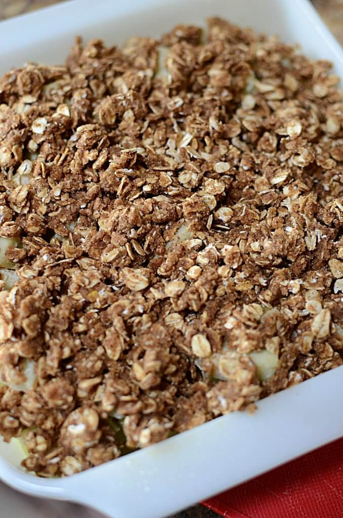 The apple crisp in a white baking dish with ready to be dished and drizzled with caramel