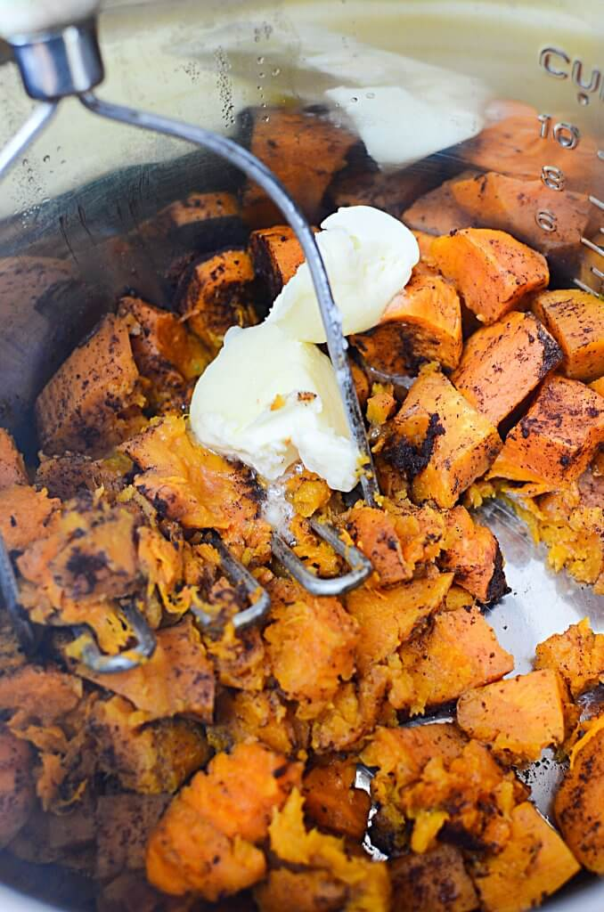 A vintage potato masher mashing up cubed and cooked sweet potato that has cinnamon sprinkled over it.