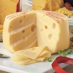 A wheel of swiss cheese resting on a white cheese board.