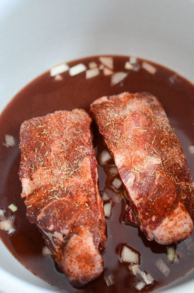two raw and seasoned beef short ribs resting in cooking liquids in the ninja foodi