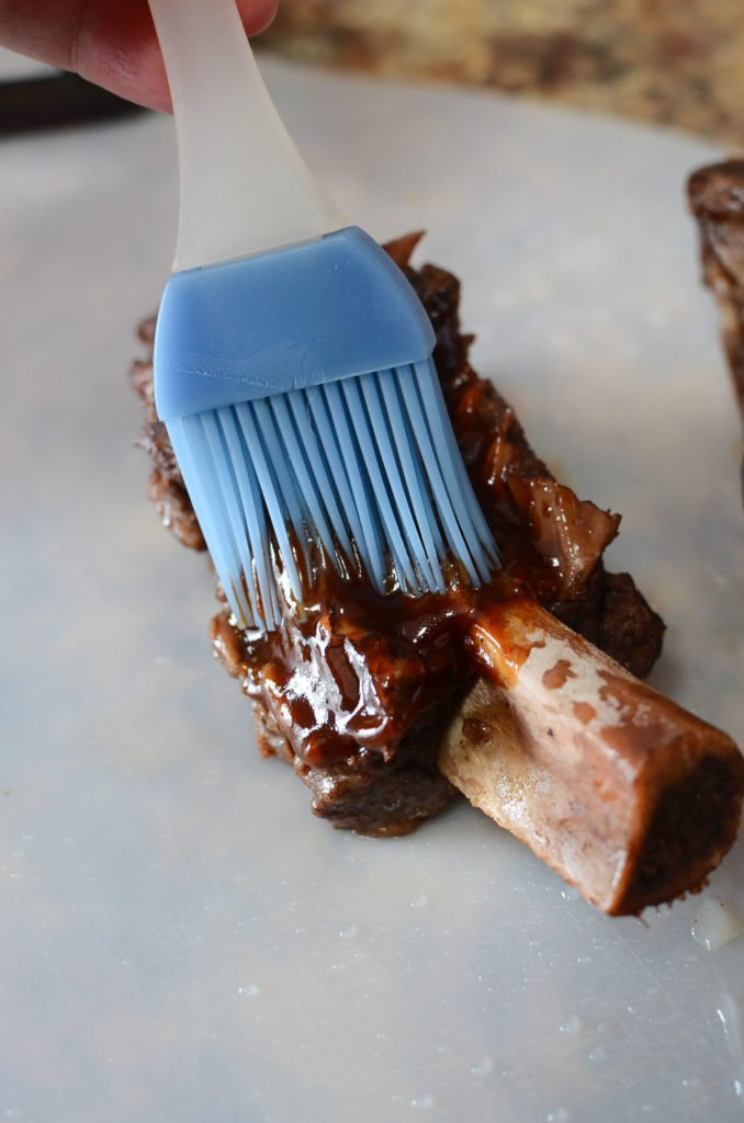 a blue silicone bbq brush, brushing bbq sauce over a beef short rib
