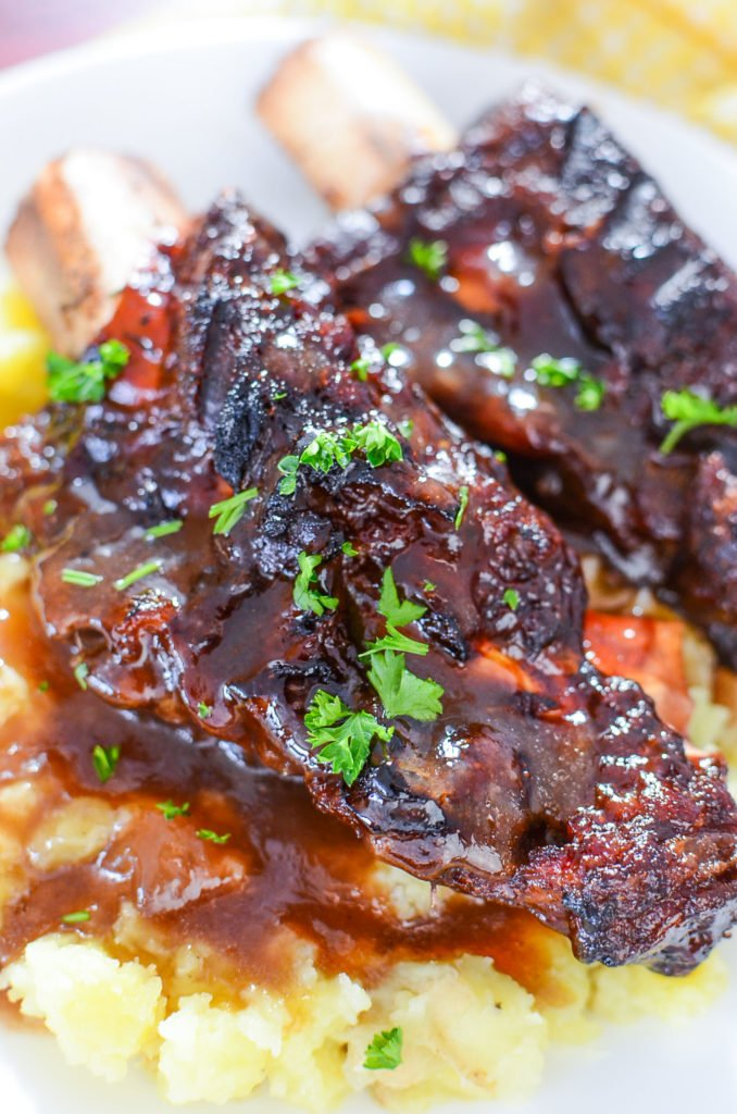 A super close up of two pressure cooked bbq short ribs with gravy over mashed potatoes