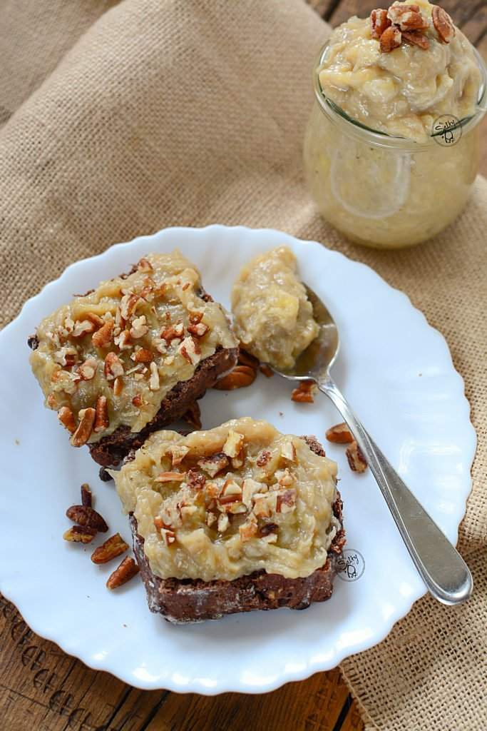 Instant pot maple banana butter on chocolate scones with pecans on top, on a white plate with a jar of the spread in the background.