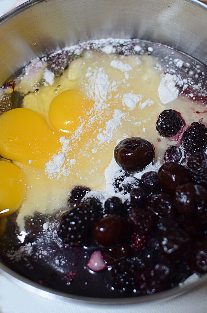 berry poke ingredients of eggs and cherries in a sliver bowl