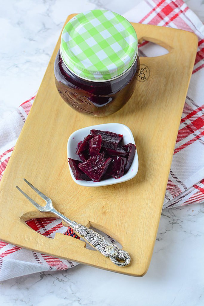 A small amount of beet pickles sitting on a white plate with a jar of the beets beside it.