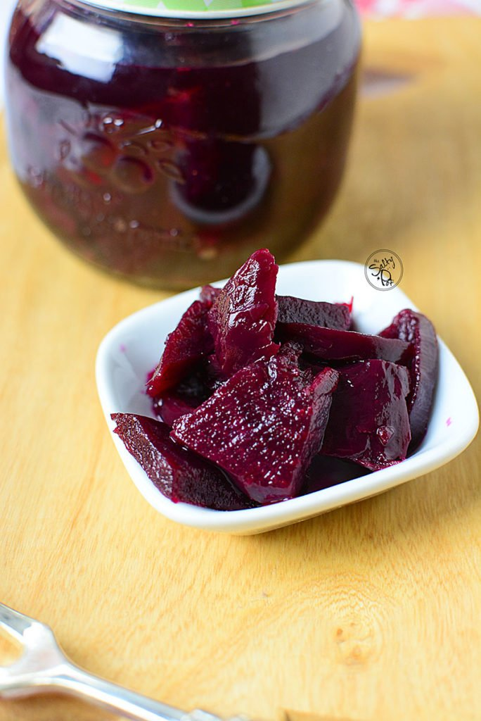 A close up, side view of the refrigerator beet pickles, sitting in a small white bowl.