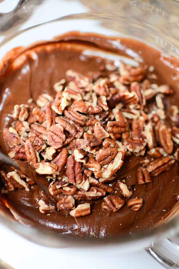 A mixture of some peanut butter and chocolate frosting , and pecans, in a bowl
