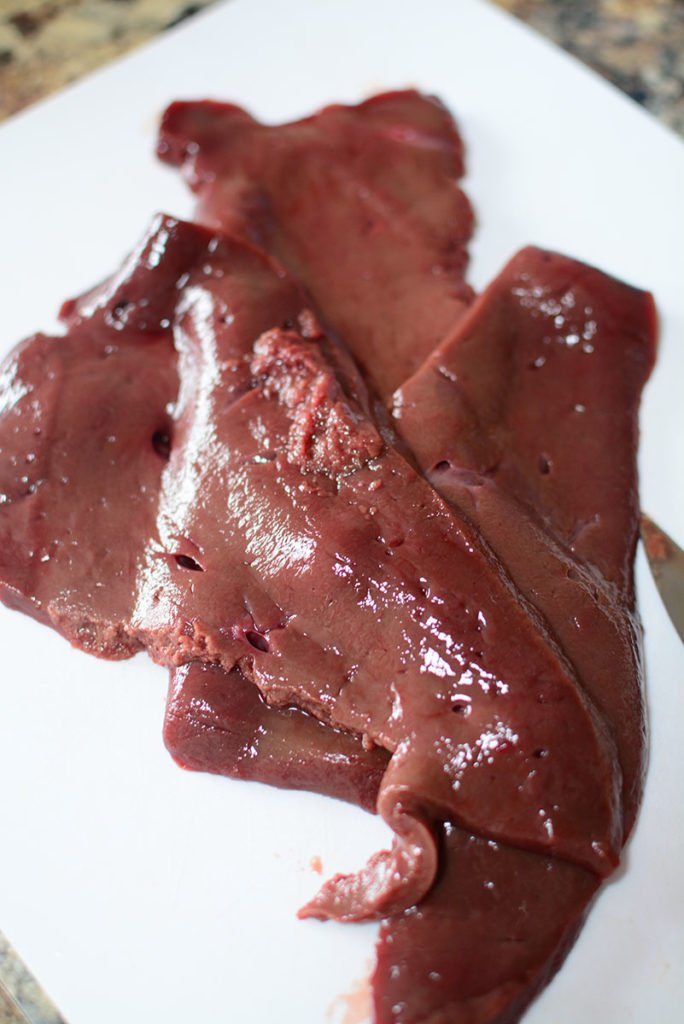 An image of fresh beef liver sitting on a white plate