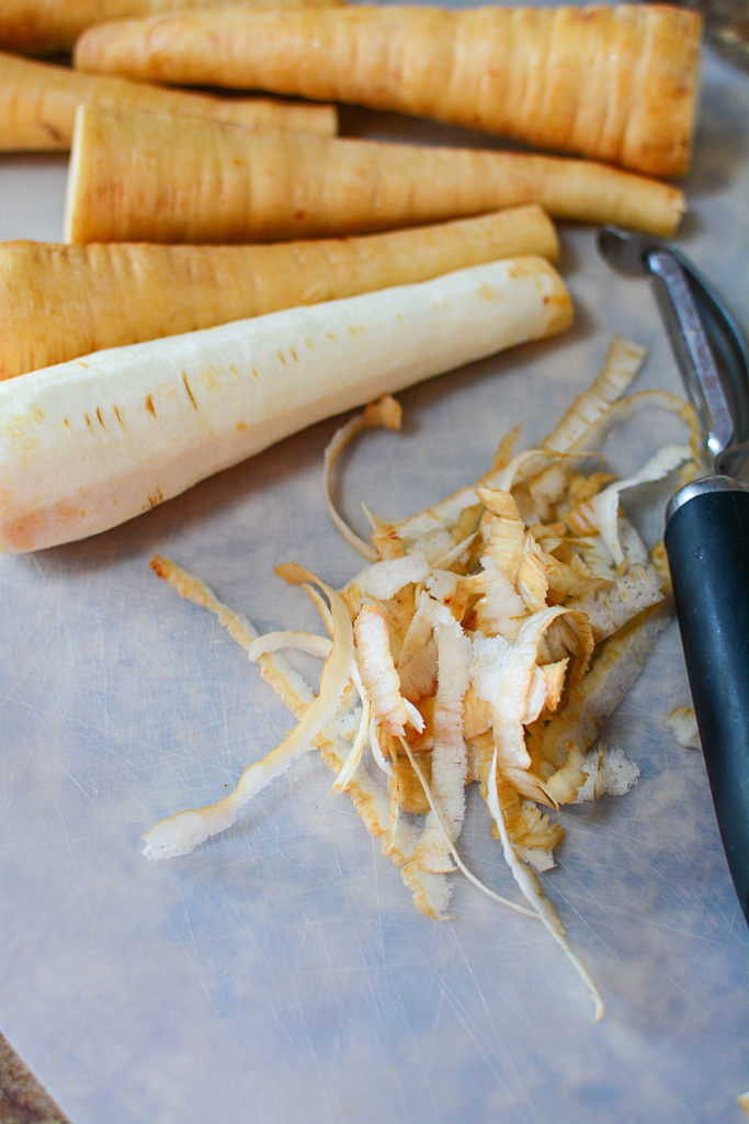6 pieces of fresh parsnips, one piece is already peeled. The peelings are on the middle, and beside them is a peeler.