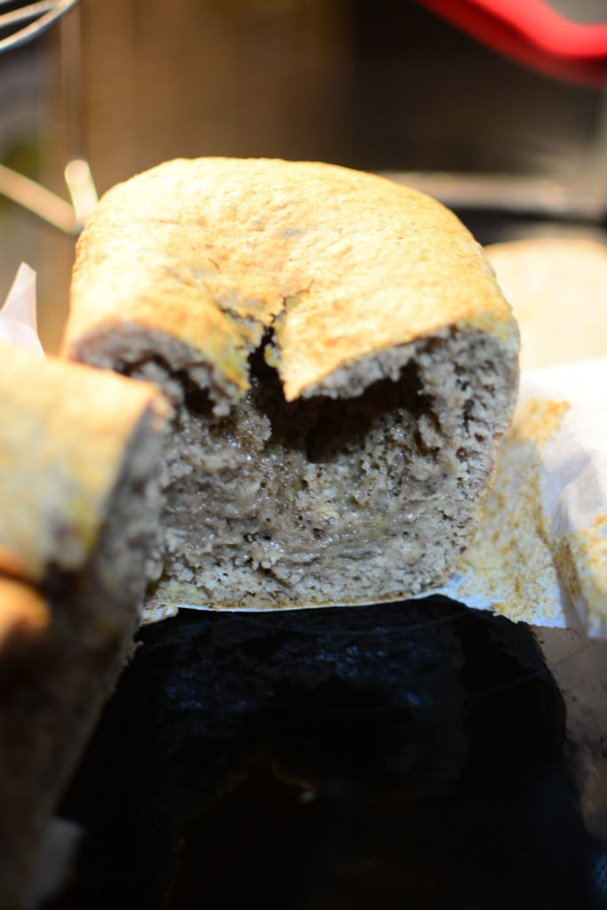a banana loaf that is cut in half with a hollow center because the center of the loaf is falling