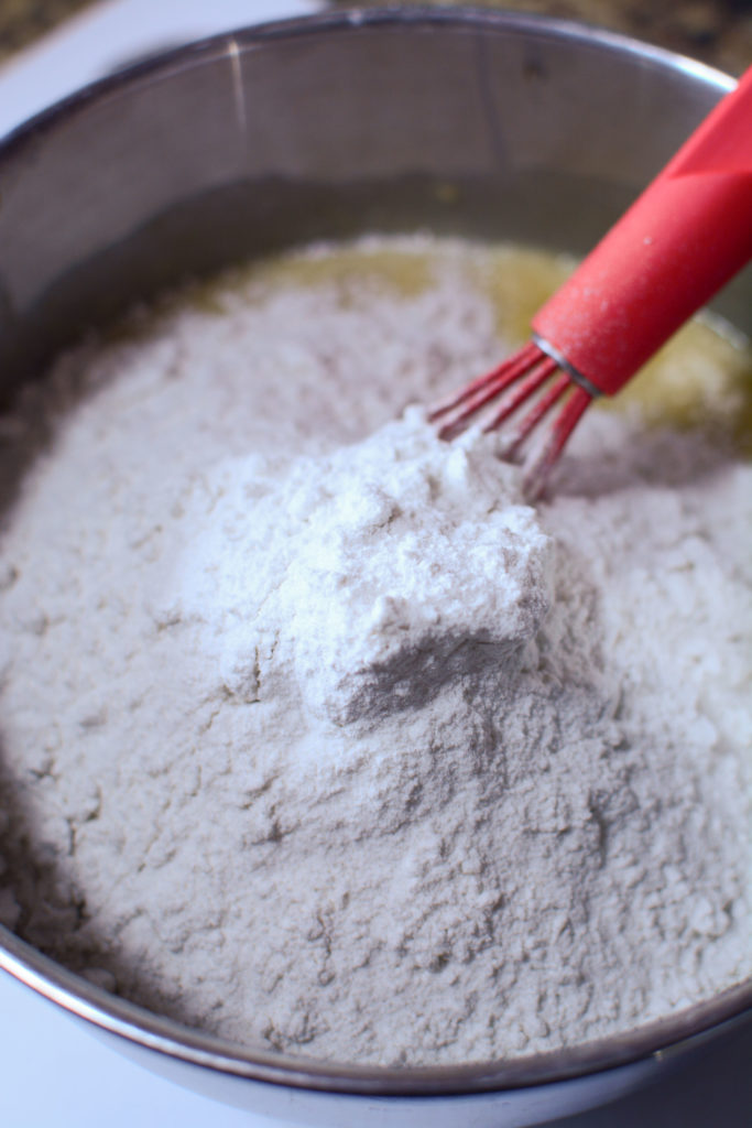 wet ingredients mixed with dry ingredients using a red whisk