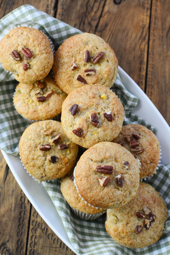 12 banana pecan muffins, with pecans on top, on a white serving plate waiting to pair with a cup of coffee!