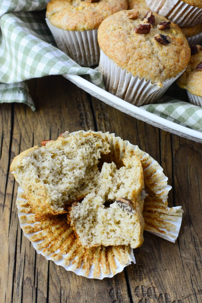 A banana muffin cut in half still sitting in the white paper liner, with whole muffins in a dish behind it.