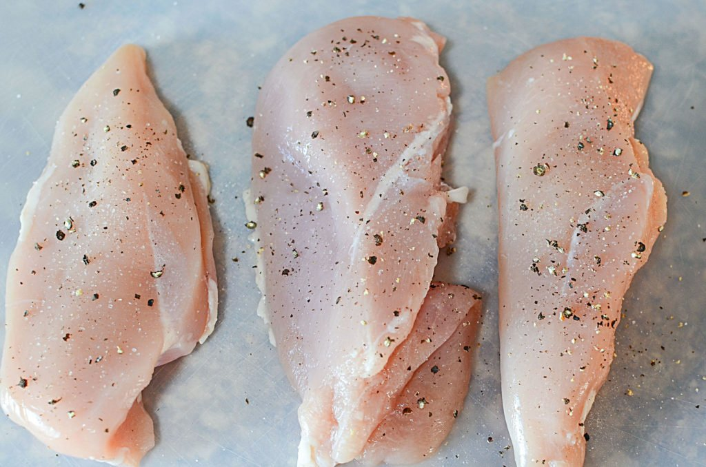 Three pieces of boneless and skinless chicken breasts with pepper sprinkled on them