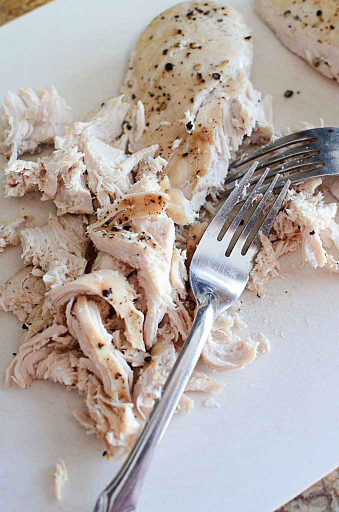 Slow cooked boneless and skinless chicken breasts on a white chopping board that are already pulled using two forks