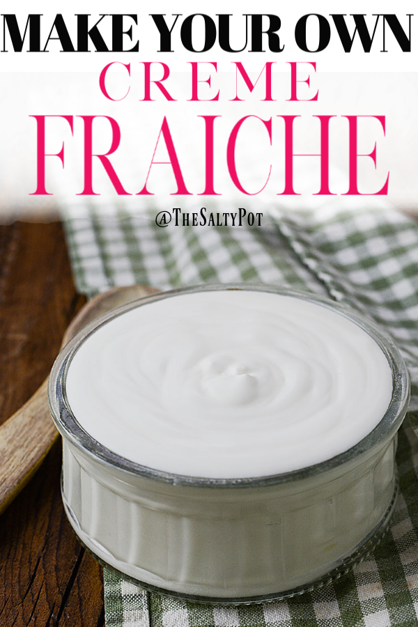 """A Pinterest pin (vertical image) of a small bowl of home made CREME FRAICHE sitting on a green and white checkered table cloth with a small wooden spoon next to it with the title """"Make your own creme fraiche"""" and """"@thesaltypot"""" below the title"""