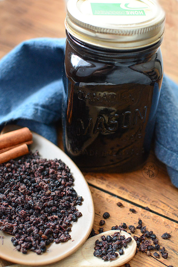 A jar of elderberry syrup with lid. Behind the jar is a piece of navy blue cloth. Beside it is plate of dried elderberries with a few cinnamon sticks on the side. Next to it is a wooden spoon with some dried elderberries