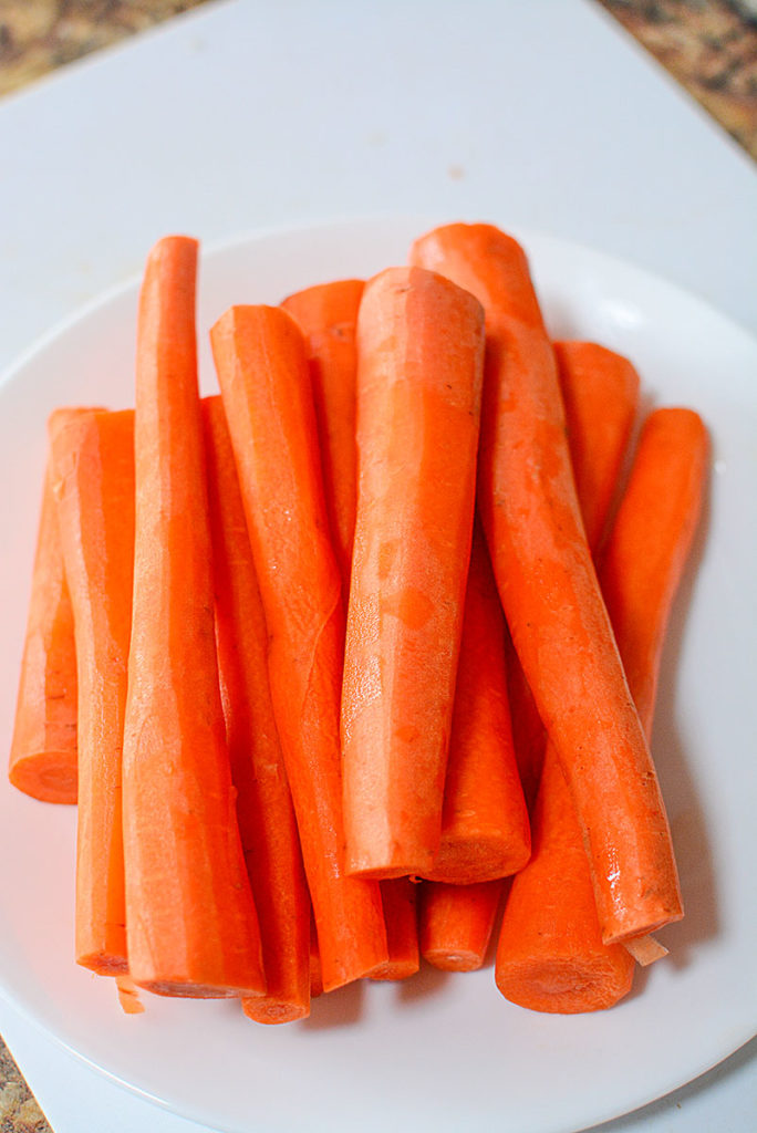 13 pieces of fresh peeled carrots sitting on a white circle plate