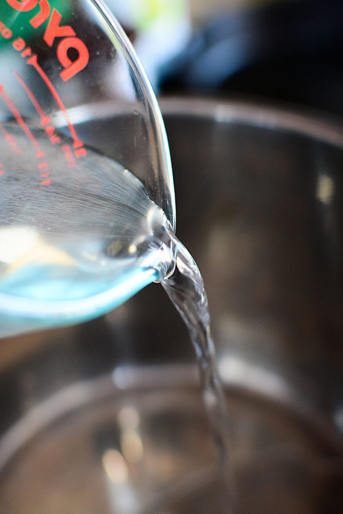 Water from a glass measuring cup being poured into a deep pot