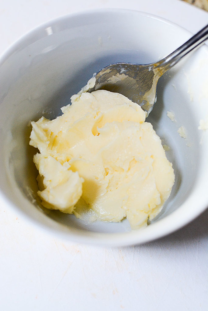Some softened butter on a bowl with spoon