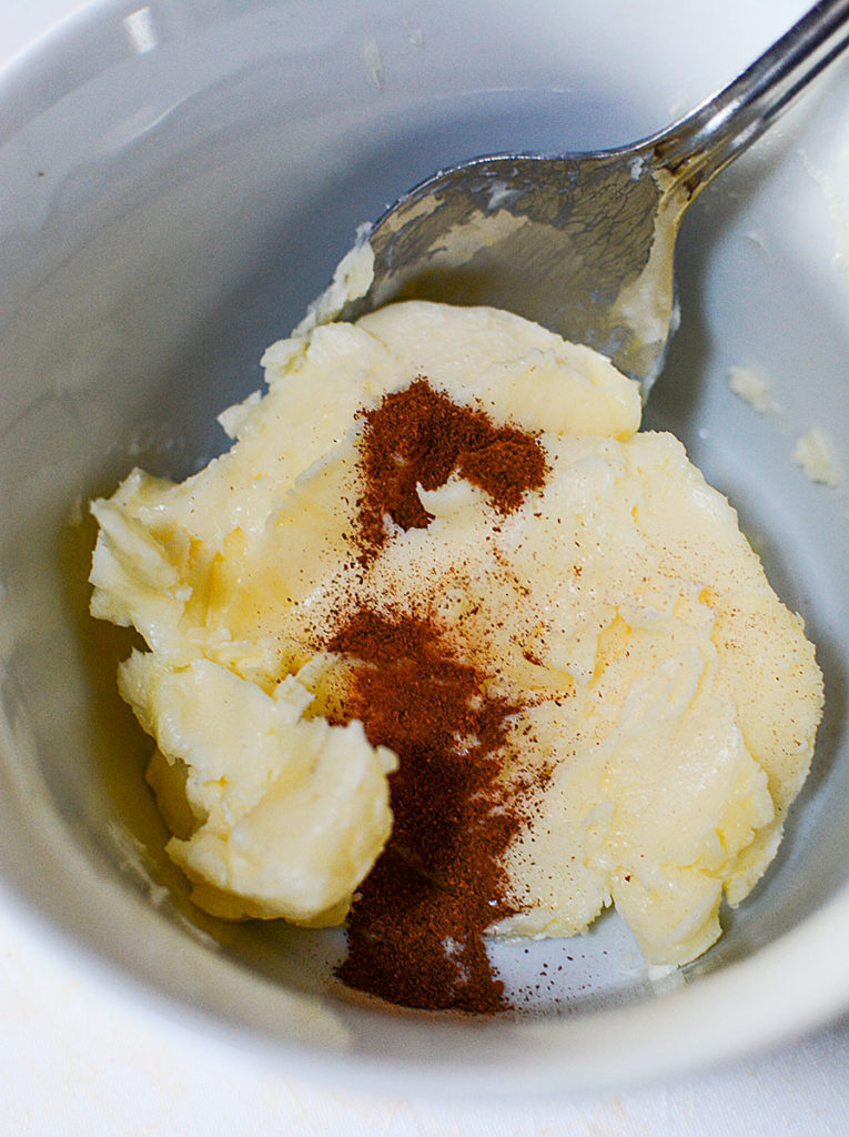 Some softened butter topped with cinnamon on a bowl with spoon