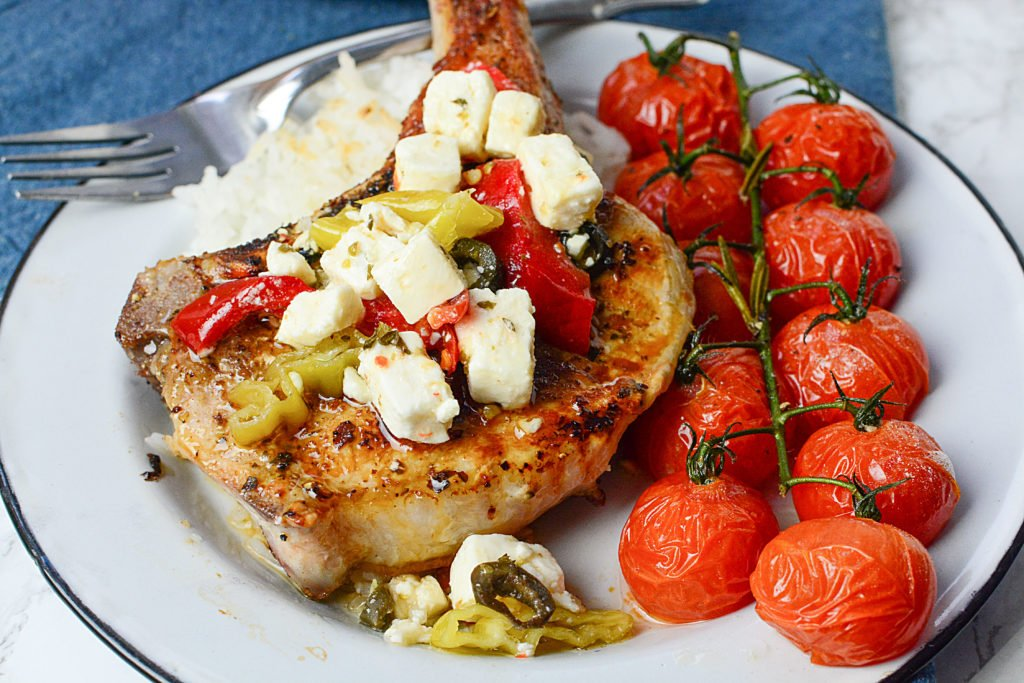 A huge piece of GRILLED MEDITERRANEAN PORK CHOPS topped with pieces of cheese and peppers sitting on steamed rice with ten pieces of roasted vine tomatoes on the side. The dish is served in a white circle plate with a fork on the side of the plate. The plate is sitting on a navy blue cloth.