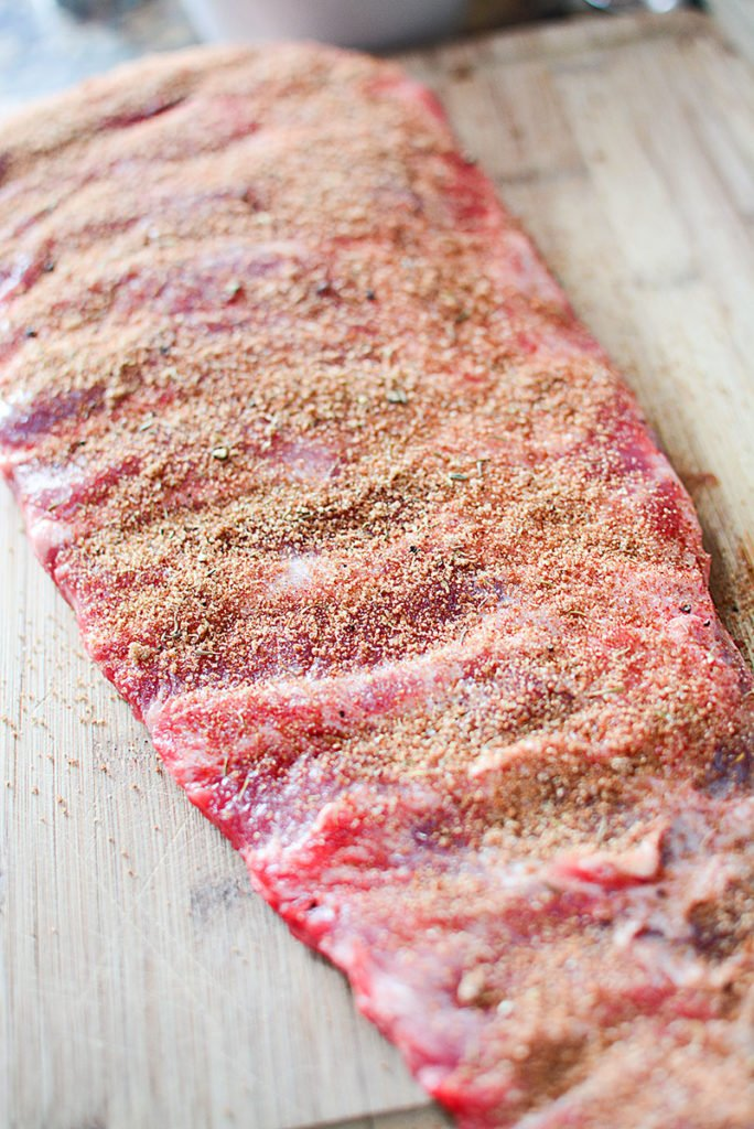 A long piece of fresh ribs with seasonings on top, laid out on a wood chopping board.