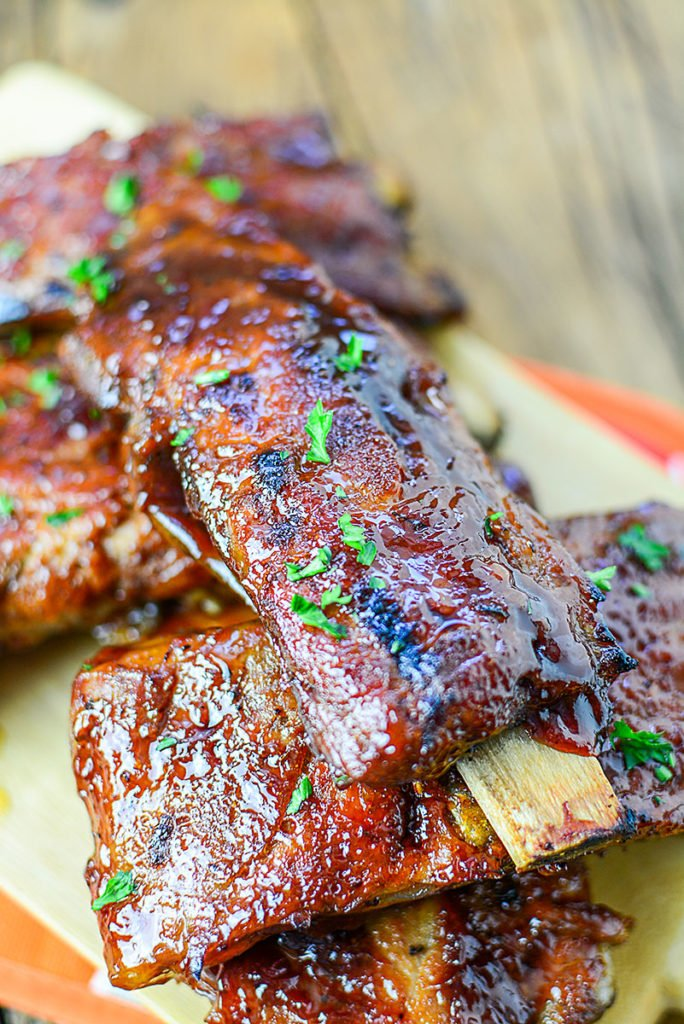 Close up image of 5 pieces of OVEN ROASTED LOW AND SLOW BBQ RIBS sitting on a wooden chopping board, garnished with some chopped parsley.