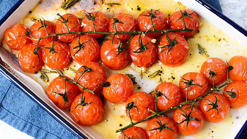 Roasted red tomatoes on a vine sitting in a white baking dish with oil and seasonings around it