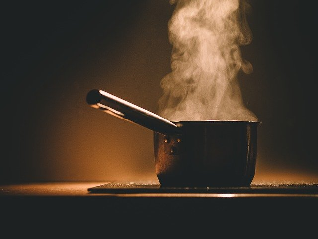 An image of a pot with a long handle on top of a stove. The liquid in the pot is steaming, you can see the smoke coming out of the pot