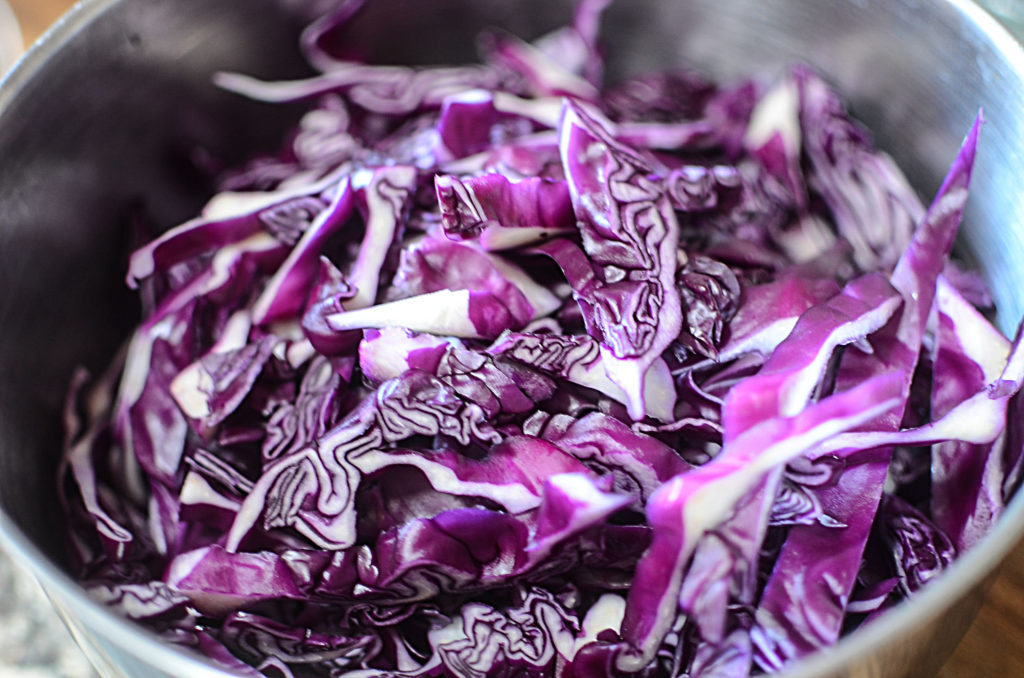 A close up image of chopped red cabbage on a stainless bowl