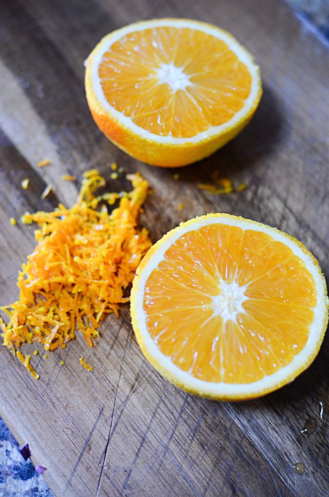 An image of an orange cut in half on top of a wood chopping board. Beside it is some orange zest.