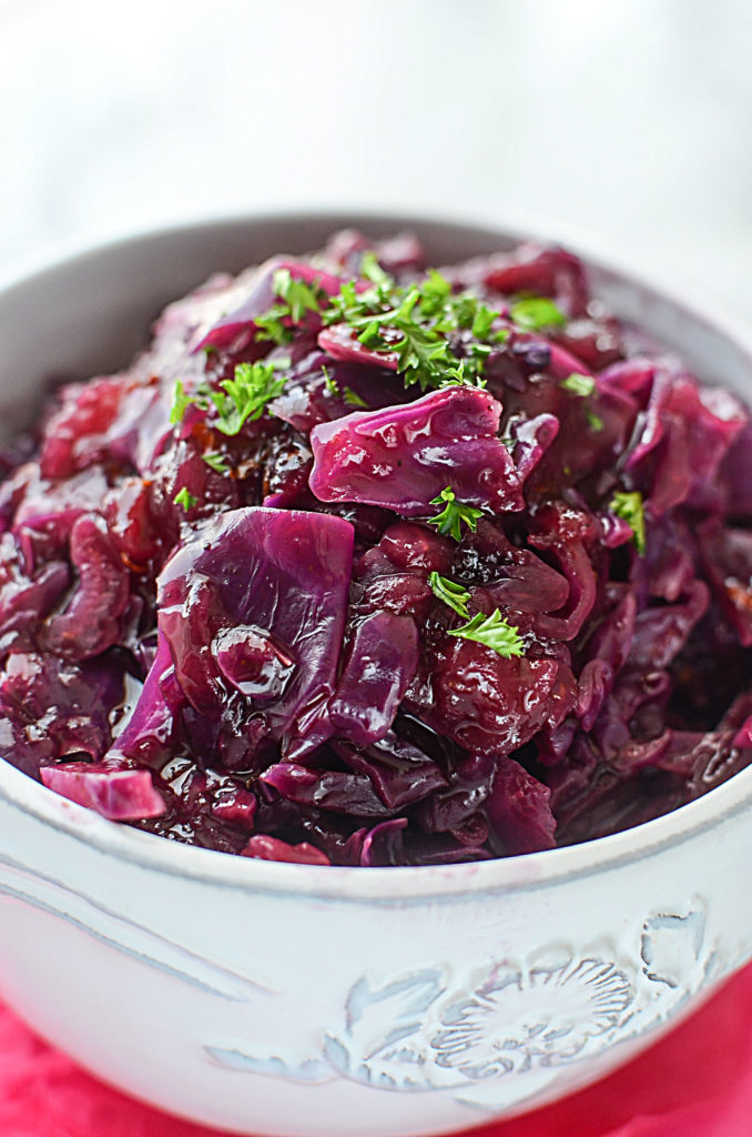 A close up image of INSTANT POT SWEET AND SOUR CABBAGE in a white bowl garnished with some chopped parsley