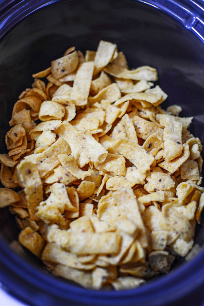 Regular plain corn chips sitting in a black slow cooker bowl ready to be seasoned