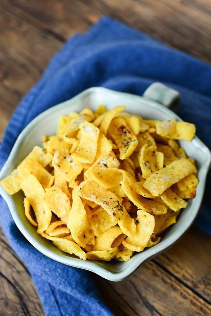 Buttery ranch corn chips on a bowl topped with salt, pepper, and other seasonings. The bowl is sitting on a piece of blue cloth.