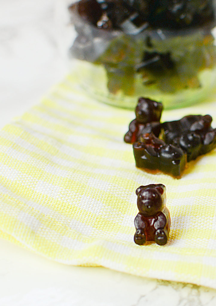 An image of elderberry syrup gummies shaped like little brown bears laid on a plaid yellow and white piece of cloth. Background is a bowlful of elderberry gummies