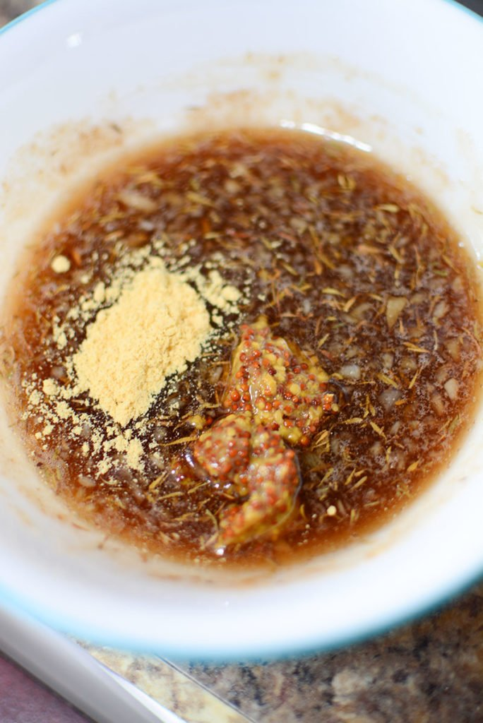 A small white bowl with some brown sugar, dried thyme, grated ginger, oil, honey, mustard powder. and seedy mustard.