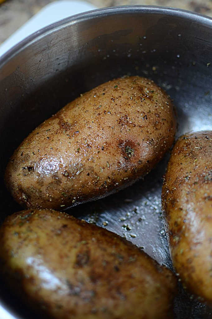Three pieces of big fresh potatoes in an empty pot, rubbed with some oil, pepper, and Italian seasoning.