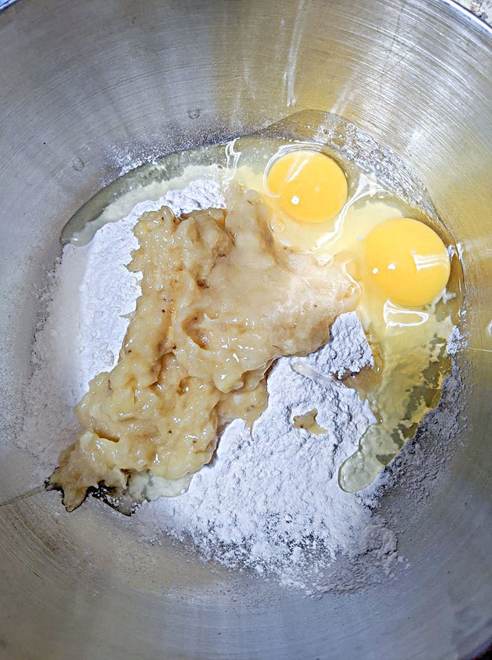 flour, mashed banana and eggs in a silver bowl