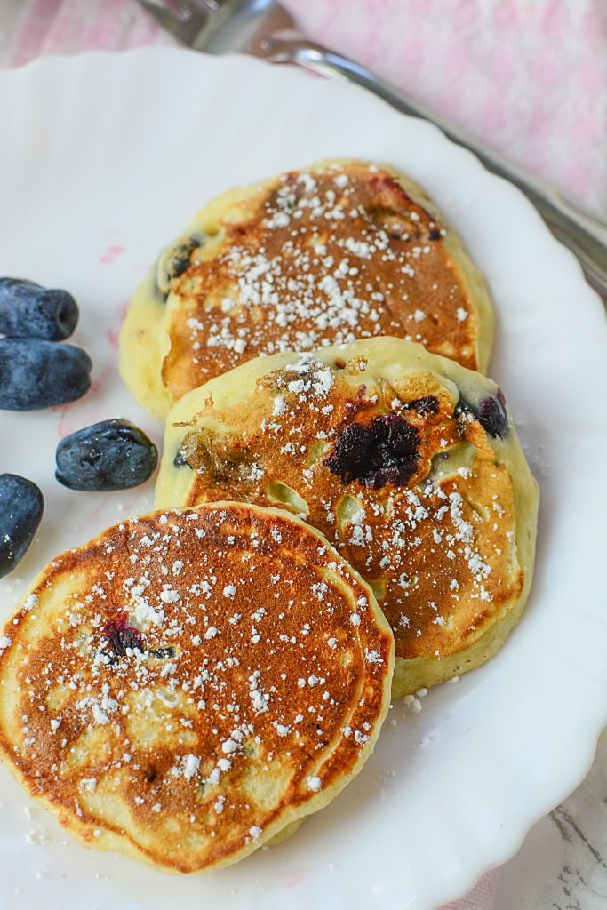 Honey berry pancakes on a white plate next to four honey berries