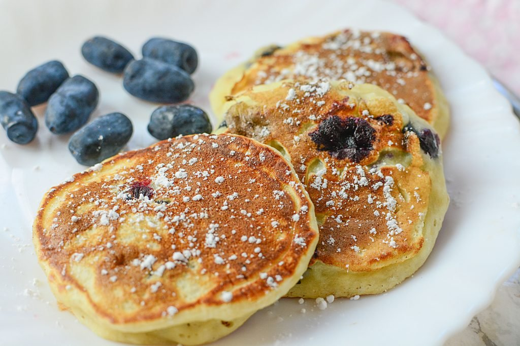 Honey berries on a plate next to three toddler sized pancakes