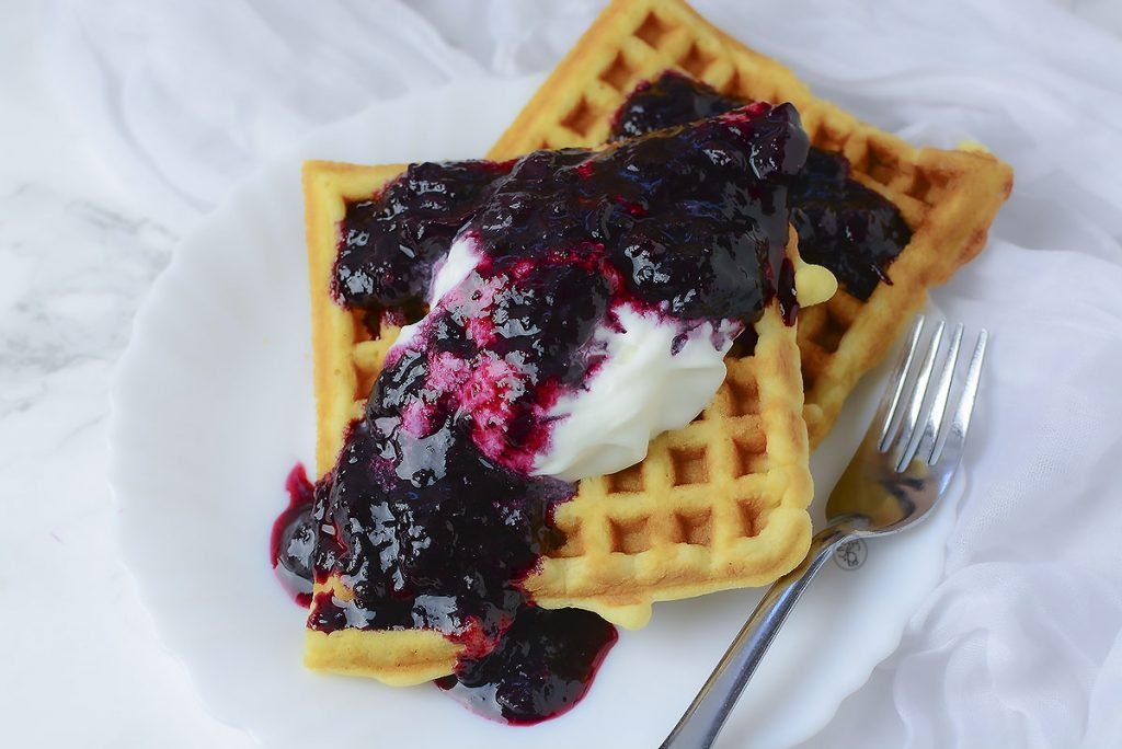 Delicious crispy waffle served with whipped cream and blueberry sauce