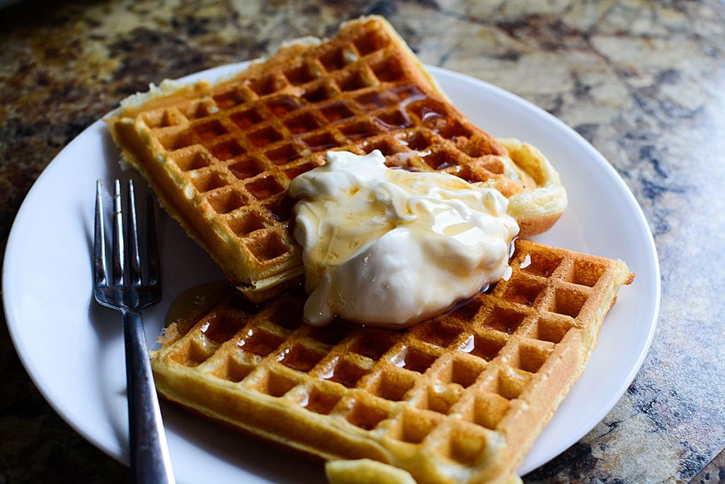 A closeup photo of the fluffy buttermilk waffles with creme fraiche and warm syrup on top!