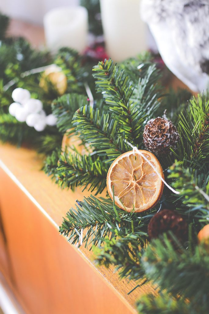 Pretty dried oranges on a string weaved in between a green garland - This sings Christmas!