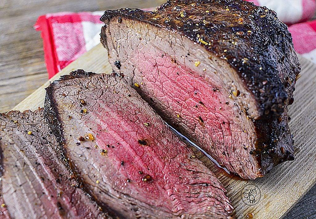 This roast beef looks so juicy sitting on the wood board!