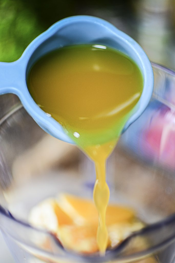 Mango juice being poured into the blender from blue tupperware measuring cups!