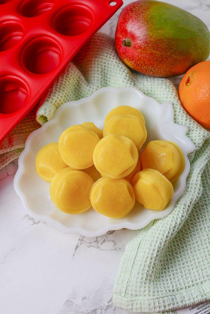 Mango orange gummy treats sitting in a white dish ready to be enjoyed!