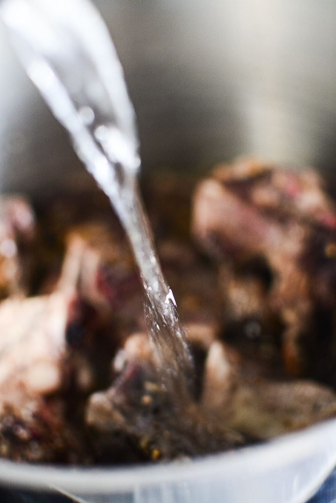 Pouring water into the roasted beef bones to make stock.