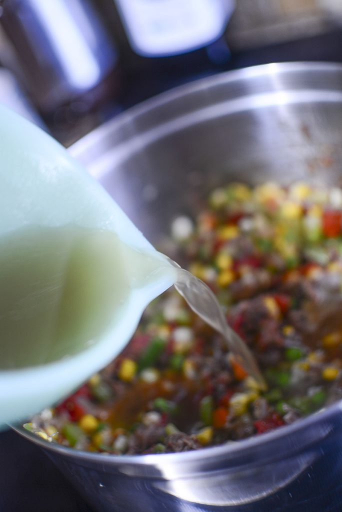 Pouring the beef stock into the soup pot.